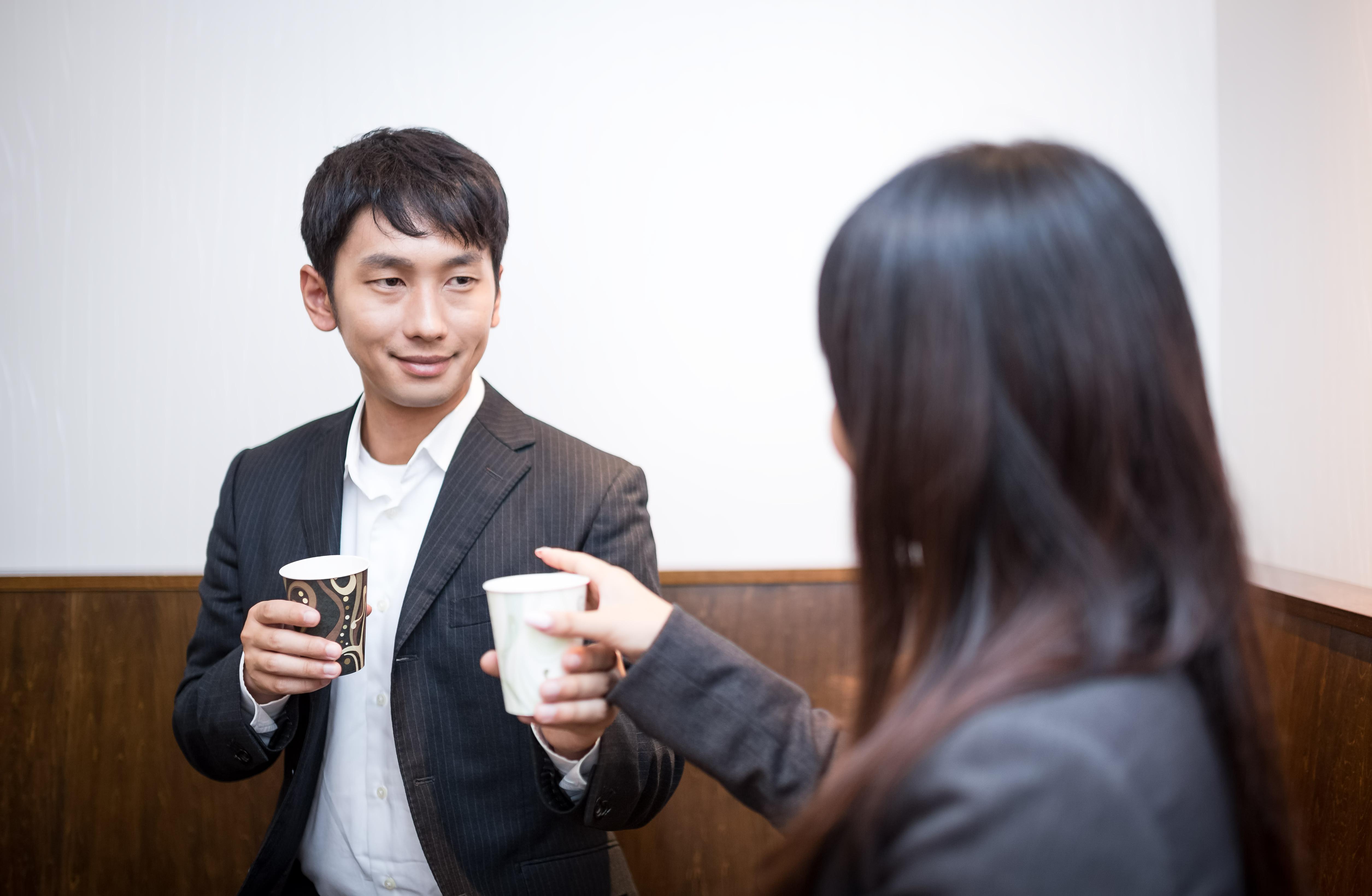 コーヒー片手に休憩する男女